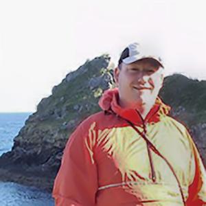 A photo of Geoff Bush standing by the New Zealand coast in a lovely orange waterproof
