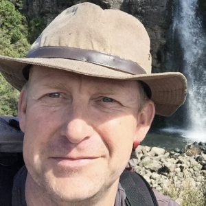 A photo of Stew Darling wearing a hat by a waterfall